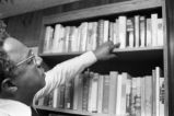 Alex Haley: Seated at bookcase, director's chair (AHP 2-79-10 #64)