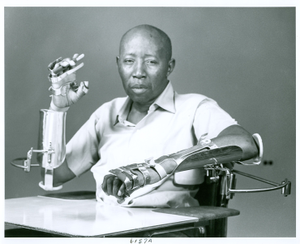Photograph of an African American male patient wearing hand splints while seated in a wheelchair with mobile arm supports and a lapboard at the Georgia Warm Springs Foundation, Warm Springs, Meriwether County, Georgia, 1971