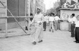 Japan, African American soldier walking on Tokyo sidewalk