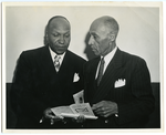 """Frederick M. Roberts standing with unidentified man while they both look at a document, """"Kill This Ad On Nov 5"""""""