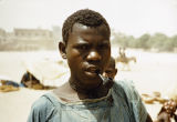 Mali, young Songhai man smoking pipe in Timbuktu