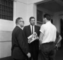 Three men speaking together at the Greyhound station in Birmingham, Alabama, after the arrival of the Freedom Riders.