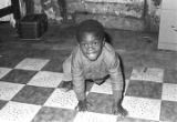 Young son of Mrs. Mary Thomas Derico, crouching on a tiled floor.