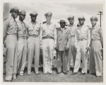 Tuskegee officers posing with their base commander Noel F. Parrish (4th from left) and unidentified man