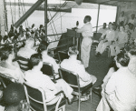 African American chaplain standing at the podium and conducting the religious service on deck of a U. S. Coast Guard vessel, South Pacific