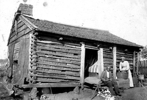 African-American man and woman in front of log house