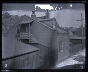 A view showing a brick house from the back alley.