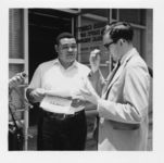 Mississippi State Sovereignty Commission photograph of Lawrence Guyot speaking into a microphone while talking to a reporter in front of the Hinds County Department of Public Welfare office during a demonstration for welfare rights in Jackson, Mississippi, 1960s