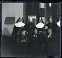 Three nuns, two women and five children posing in front of windows, Springfield, Minnesota