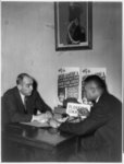 [Two men seated in conversation at desk with posters announcing upcoming equal rights demonstration at Madison Square Garden, New York City, June 16th]