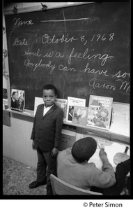 Young boy at the blackboard beneath the sogan 'Soul is a feeling, anybody can have it': Liberation School, Boston, Mass.