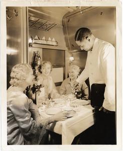 African American waiter serving three women in Pullman car : photoprint