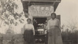 Two African American woman standing outside a small wooden outbuilding filled with jars of preserves, in rural Madison County, Alabama.