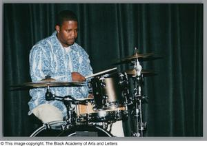 Photograph of a man playing a small drum set Hip-Hop Soul Cabaret