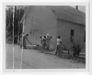 Photograph of African American men and women raking land by a wooden building, Clarkesville, Habersham County, Georgia, 1953
