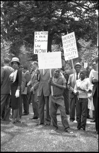 Young protesters holding signs demanding racial equality and fair employment in Washington, D.C. Signs read 'American patriots support racial equality NAACP' and 'DC needs a fair employment law now'