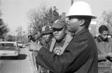 Wendell Paris and other students from Tuskegee Institute lined up along a street during a demonstration to protest the murder of Samuel L. Younge, a civil rights worker.