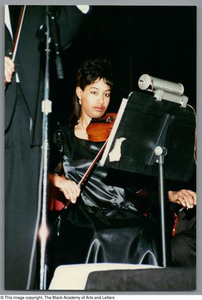 Photograph of a young girl playing her instrument Christmas/Kwanzaa Concert Hallelujah Hip Hop Concert, December 1995