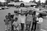 Woman and children standing in United Durham Incorporated Super Market parking lot.