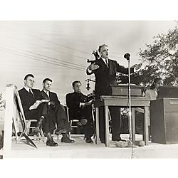 Groundbreaking ceremony with man speaking, three men and a woman organ player on outdoor platform