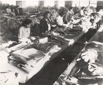 """Jersey City Quartermaster Repair Sub-Depot; Negro women play an important part in the conservation activities of the Quartermaster Corps.; Overcoats, shirts, trousers, and other items are prepared for final repair operations by ripping off torn pocket flaps, sleeves, and other portions of garments and replacing with patches or new portions; This is termed 'preparation""""; Approximately 100 employees are engaged in preparing clothing similar to view shown in photograph"""