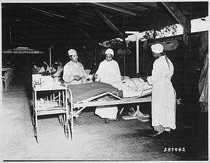 """Surgical ward treatment at the 268th Station Hospital, Base A, Milne Bay, New Guinea. Left to right: Sgt. Lawrence McKreever, patient; 2nd Lt. Prudence Burns, ward nurse; 2nd Lt. Elcena Townscent, chief surgical nurse; and an unidentified nurse."""