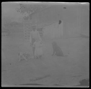 A boy standing behind a child in the yard of the J.H.P. Davis house