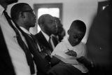 Man and little boy in the audience at Mt. Moriah Baptist Church in Hayneville, Alabama, during the first anniversary celebration of the Lowndes County Christian Movement.