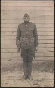 [Unidentified African American soldier in uniform and overseas cap with canteen and knife hanging from cartridge belt]