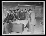 Negro aviators, Tuskegee, Alabama. Basic & Advanced Flying School Lt. Donald B. McPherson, Air Corps Director of Basic Training explaining a cross country flight on map in classroom as cadets look on.