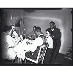 5 people seated at dinner table with one man standing