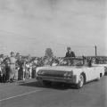 President John F. Kennedy riding in a convertible past a crowd at the Redstone Army Airfield in Huntsville, Alabama.
