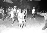 Adults and children marching down the street beside an apartment building at Cleveland Court in Montgomery, Alabama, during a civil rights demonstration.