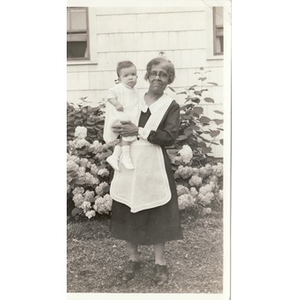 A housekeeper holds a young infant.