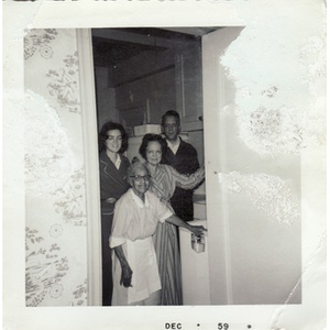 An elderly housekeeper poses with her employers.