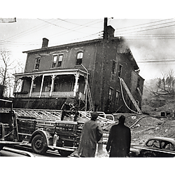 Two men observing burning brick house with fire ladders and fire truck in street