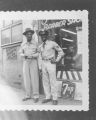 Two African-American men, one in military uniform, standing outside a barber shop, ca. 1940's-1950's