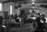 Norman Lumpkin speaking to an audience in a small wooden church building in Prattville, Alabama, probably during a meeting of the Autauga County Voters Association.