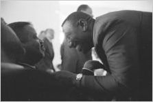 Albert Turner speaking to Ralph Abernathy at a large gathering, probably at First Baptist Church in Eutaw, Alabama.