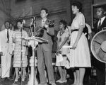 Photograph of mass meeting, Fisk University, Nashville, Tennessee, with Guy Carawan leading song on guitar, 1960 April 21
