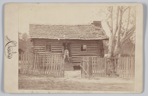 Albumen print of a woman and two children in front of a log house in Georgia