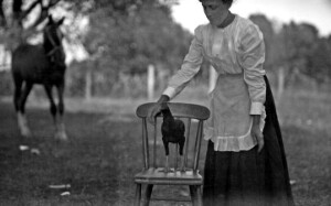 Unidentified woman with a chicken on a chair.