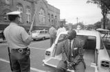 African American man seated on the tailgate of an ambulance parked beside 16th Street Baptist Church in Birmingham, Alabama, after the building was bombed.