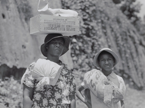 Two Negro women carrying packages, one has a box of surplus relief commodities on her head. Natchez, Mississippi