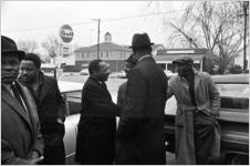 Martin Luther King, Jr., shaking hands with a man in the parking lot outside Tabernacle Baptist Church in Selma, Alabama.