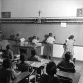 Children writing on the blackboard at the front of a classroom at Nazareth Catholic Mission in Montgomery, Alabama.