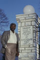Lucius Amerson, former sheriff of Macon County, Alabama, standing beside a plaque honoring him in downtown Tuskegee.