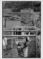 Jerome Jackson taking clothes off of his clothesline at his East Lake Meadows apartment, undated
