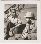 Artist Jacob Lawrence sitting on building steps with unidentified man, in Brooklyn, New York, 1941