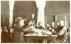 Men at table with animal carcass, Minnesota Building, Louisiana Purchase Exposition